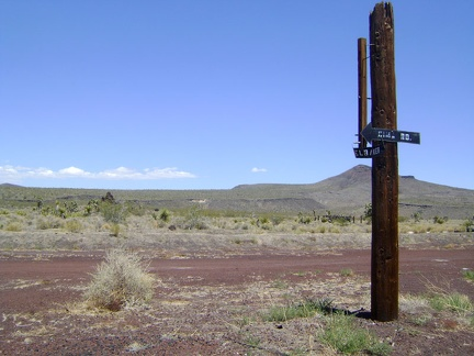 Signs on an broken old post once directed vehicles leaving Aiken Mine toward Cima Road or Kelbaker Road