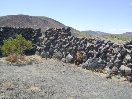 I walk back down the hill from the Aiken Mine equipment to examine a rock wall on the flats