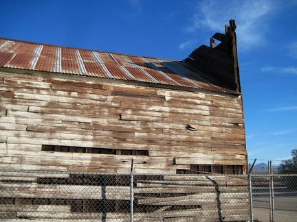 The siding of the old wooden building is peeling away as the structure sags