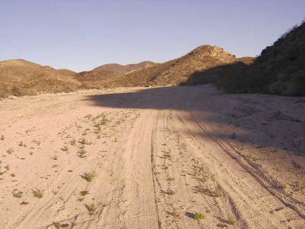 After about three miles, Indian Springs Road turns toward the hills up a sandy wash