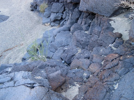 "I climb back down the volcanic rock into the wash to resume my return hike down ""South Broadwell Wash"""