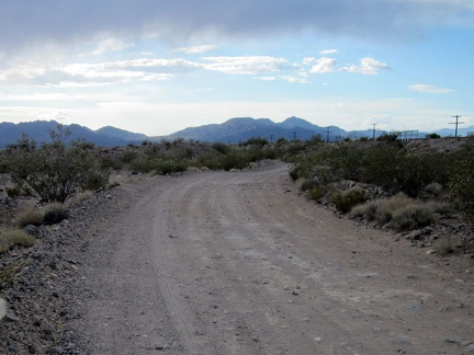 Nipton-Desert Road comes out from under a few dark clouds as I ride toward Primm