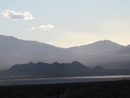 Vehicles on the I-15 freeway, on the other side of Ivanpah Valley, glisten as the setting sun peers through the clouds