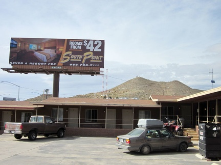"A billboard next to the Searchlight motel advertises a ""luxury"" motel elsewhere"