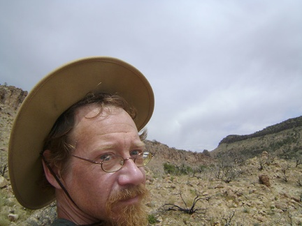 The Mojave storm clouds have brought high winds that try to blow the hat off my head